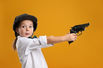 Cute little detective with revolver on yellow background