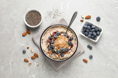 Tasty oatmeal porridge with toppings served on light grey table, flat lay