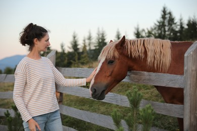 Woman stroking beautiful horse near wooden fence outdoors. Lovely domesticated pet