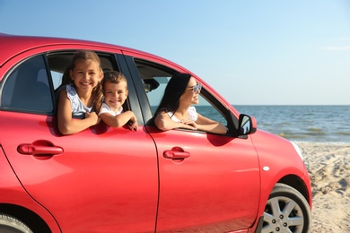 Happy woman and her children in car near sea. Summer trip