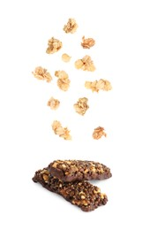 Tasty protein bars and granola falling on white background