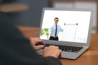 Woman having online video consultation with business trainer at table, closeup