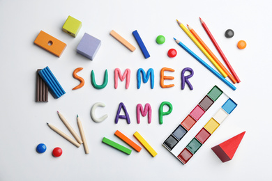 Flat lay composition with phrase SUMMER CAMP made of colorful clay on white background