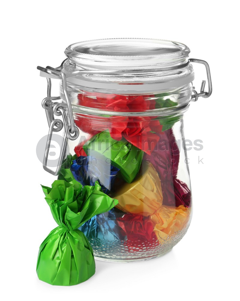 Glass jar with candies in colorful wrappers isolated on white