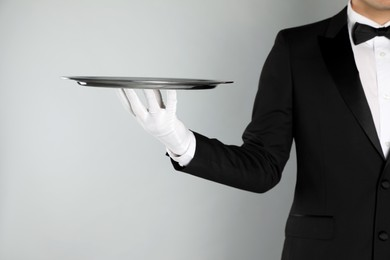 Butler with tray on light grey background, closeup