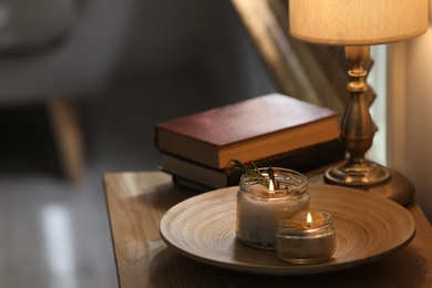 Natural homemade mosquito repellent candles on wooden table in room. Space for text