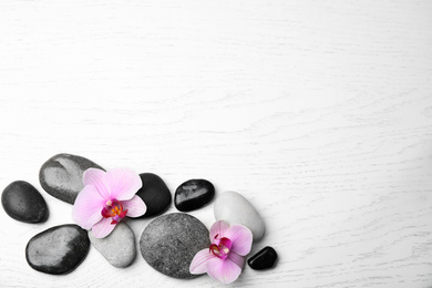 Stones with orchid flowers and space for text on white wooden background, flat lay. Zen lifestyle