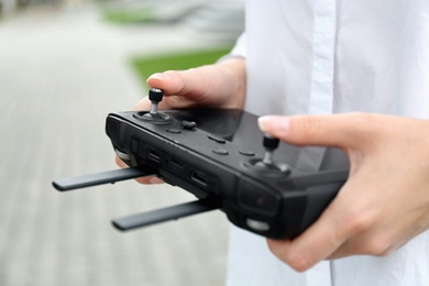 Woman with modern drone controller outdoors, closeup