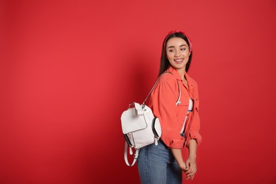 Beautiful young woman with stylish leather backpack on red background. Space for text