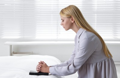 Religious young woman with Bible praying in bedroom. Space for text