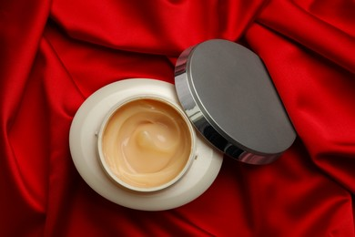 Open jar of hair care cosmetic product on red fabric, top view