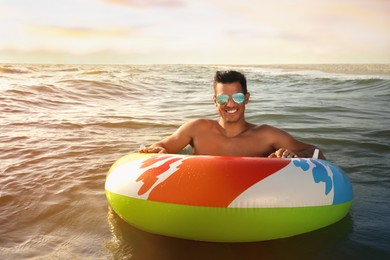 Man with inflatable ring resting in sea