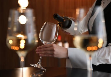 Waitress pouring wine into glass in restaurant, closeup