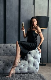Beautiful woman in elegant dress with glass of champagne on sofa indoors. Luxury lifestyle