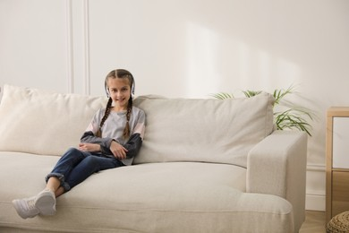 Girl with headphones sitting on comfortable sofa in living room