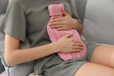 Woman using hot water bottle to relieve menstrual pain on sofa at home, closeup