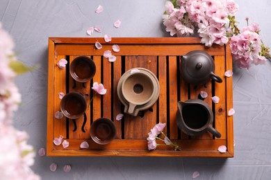 Beautiful set for traditional tea ceremony and sakura flowers on light grey table, flat lay