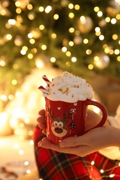 Woman holding cup of delicious drink with whipped cream near Christmas tree indoors, closeup