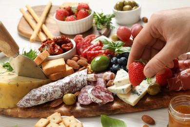 Woman taking strawberry from board with different appetizers at white wooden table, closeup