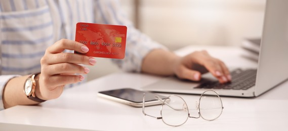 Woman with credit card using laptop for online payment at table, closeup. Banner design