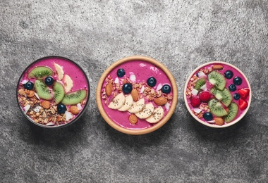 Acai smoothie bowls with granola and fruits on grey table, flat lay
