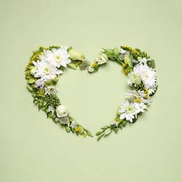 Beautiful heart shaped floral composition on light green background, flat lay