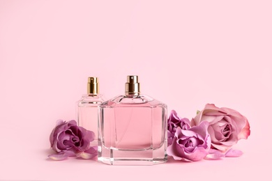 Bottles of perfume and beautiful roses on pink background