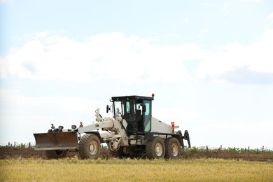 Modern agricultural machinery in field on sunny day