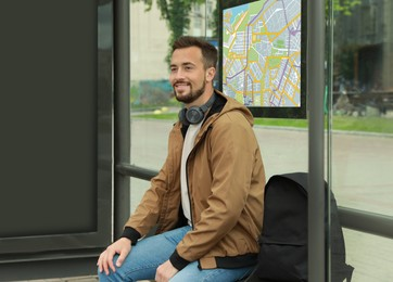 Young man with headphones and backpack waiting for public transport at bus stop