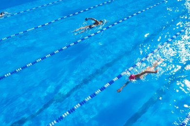 People training in outdoor swimming pool on sunny day