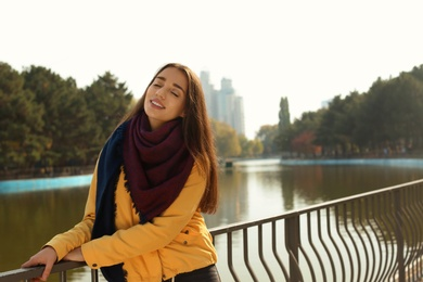 Young beautiful woman near pond in park. Autumn walk