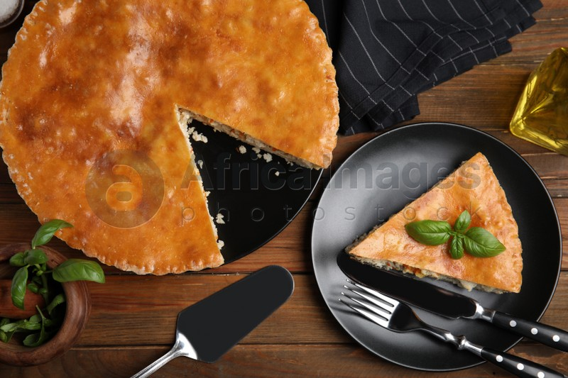 Delicious pie with meat and basil on wooden table, flat lay