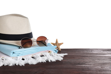 Different beach objects on wooden table against white background. Space for text