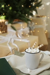Cup of cocoa with wafer tubes on table indoors. Christmas celebration