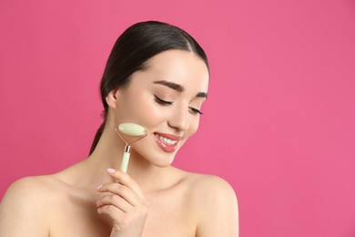 Woman using natural jade face roller on pink background, space for text