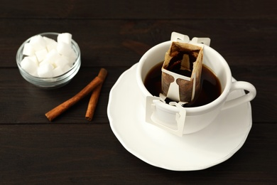 Cup with drip coffee bag, sugar and cinnamon on brown wooden table