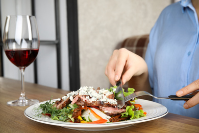 Woman eating delicious salad with roasted meat at wooden table, closeup