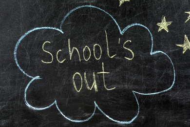 Text School's Out and drawings on black chalkboard. Summer holidays