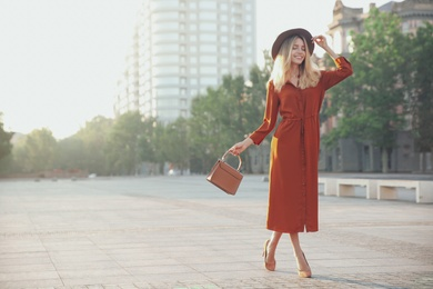 Beautiful young woman in stylish red dress and hat with handbag on city street