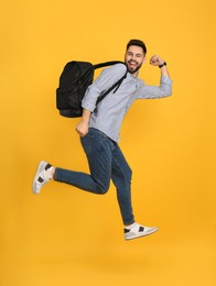 Emotional man with stylish backpack jumping on yellow background