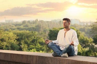 Man meditating outdoors on summer day. Space for text