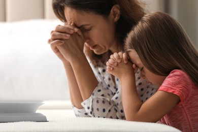 Mature woman with her little granddaughter praying together over Bible in bedroom