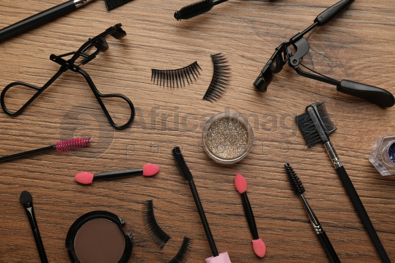 Flat lay composition with eyelash curlers, makeup products and accessories on wooden table