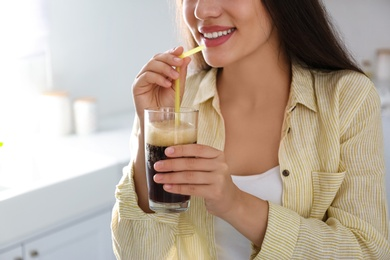 Young woman with cold kvass indoors, closeup. Traditional Russian summer drink