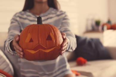 Woman holding pumpkin jack o'lantern indoors, closeup with space for text. Halloween celebration