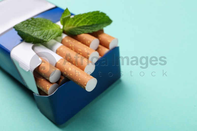 Pack of menthol cigarettes and mint on turquoise background, closeup. Space for text