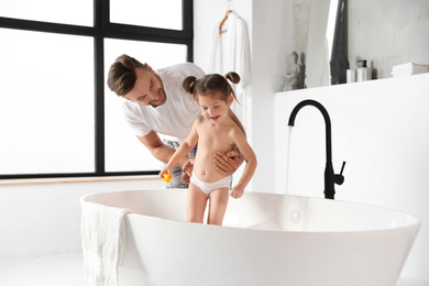 Young father with cute little daughter in bathroom