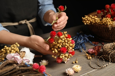 Florist making bouquet of dried flowers at wooden table, closeup