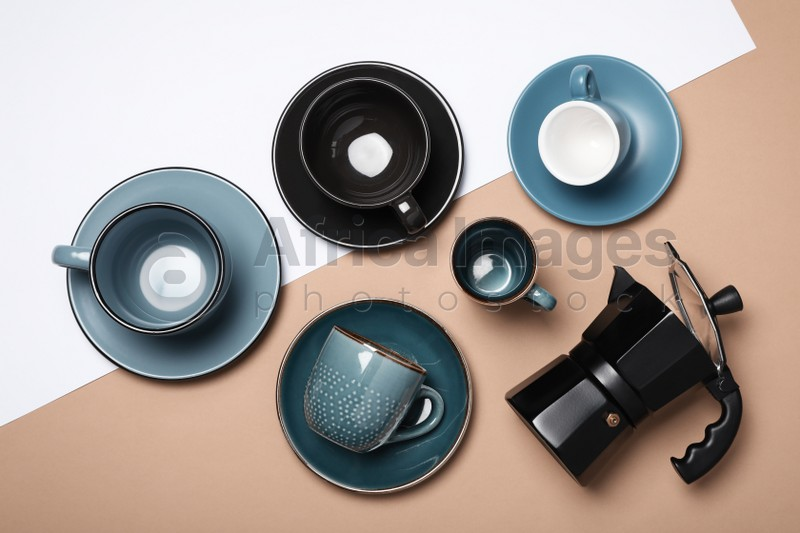 Different cups and geyser coffee maker on color background, flat lay