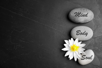 Lotus flower, stones with words Mind, Body, Soul and space for text on black background, flat lay. Zen lifestyle